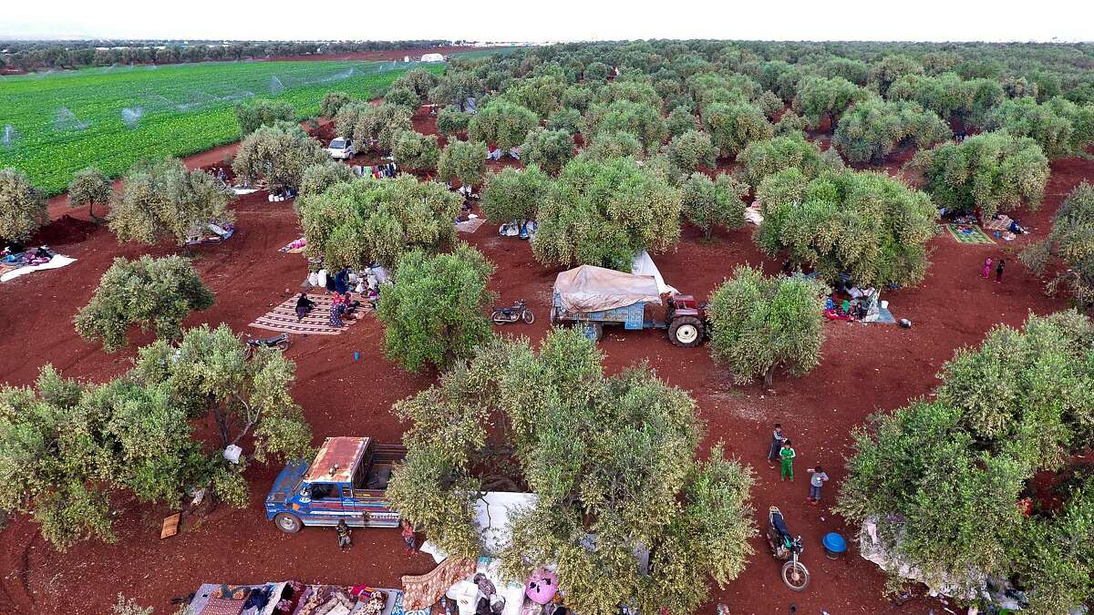 TOPSHOT - An aerial view shows displaced Syrians gathering in a field near a camp for displaced people in the village of Atme, in the jihadist-held northern Idlib province on May 8, 2019. - In the olive grove in Atme, dozens of families have spent the night on thin mattresses or blankets layed out over rugs on the red earth. At the base of the trees they have chosen for shelter, they have stored the bare minimum for a life outdoors: bedding, a water cooler, a saucepan, or a cooking gas canister. They have hung up sheets between the trees for a little privacy, and one family has even brought a solar panel. (Photo by Aaref WATAD / AFP)AAREF WATAD/AFP/Getty Images
