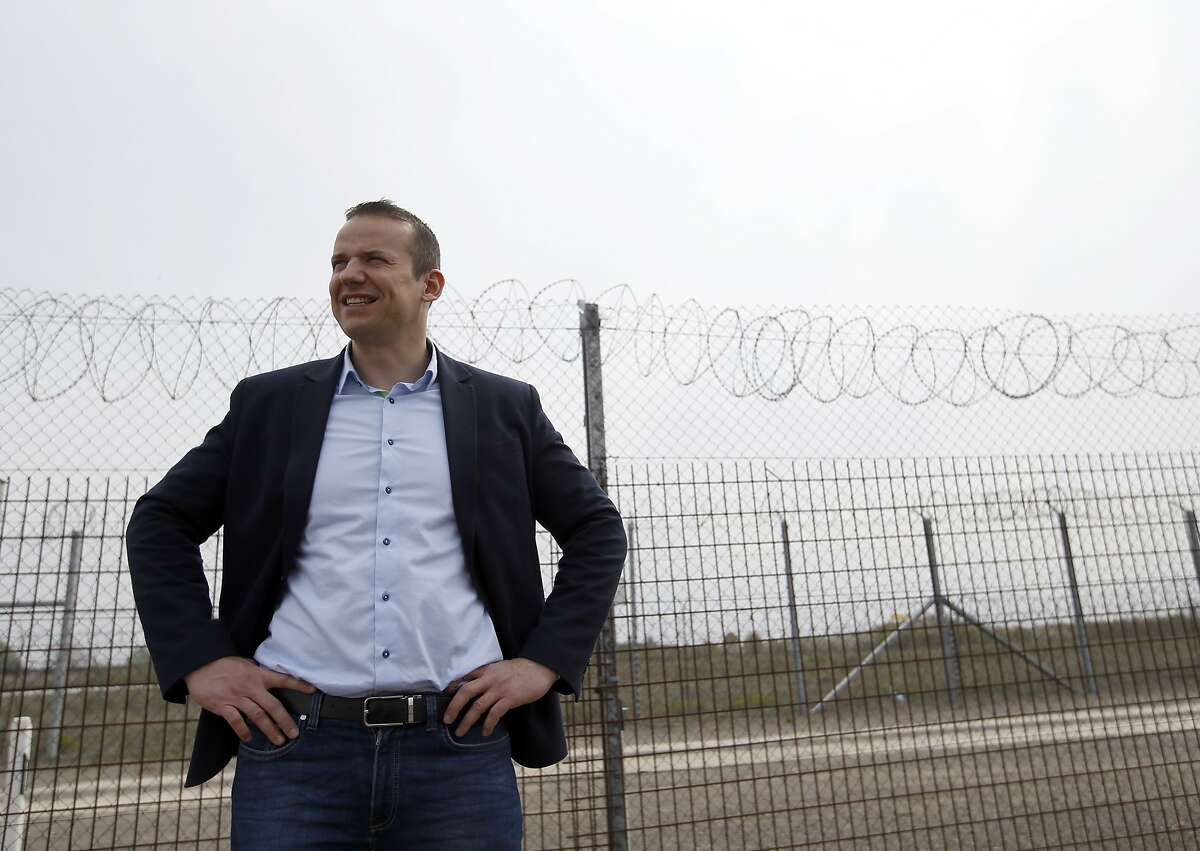 In this photo taken Monday, April 8, 2019, Asotthalom's mayor Laszlo Toroczkai speaks in front of the fence at Hungary's border with Serbia near the village Asotthalom, Hungary. With a campaign centered on stopping immigration, Hungary's ruling Fidesz party is expected to continue its dominance in the European Parliament election at the end of May. Torczkai, who is critical of government corruption and some of Hungarian Prime Minister Viktor Orban's economic policies, still appreciates the border fence that Orban built to stop migrants from entering the country. Torczkai says: