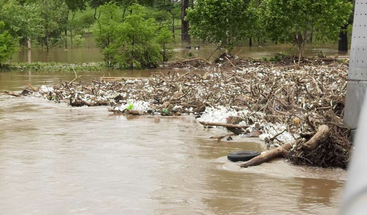 Debris and trash build up on the Carruth Pedestrian Bridge over Buffalo Bayou west of downtown Houston after heavy rains on Friday, May 9, 2019.