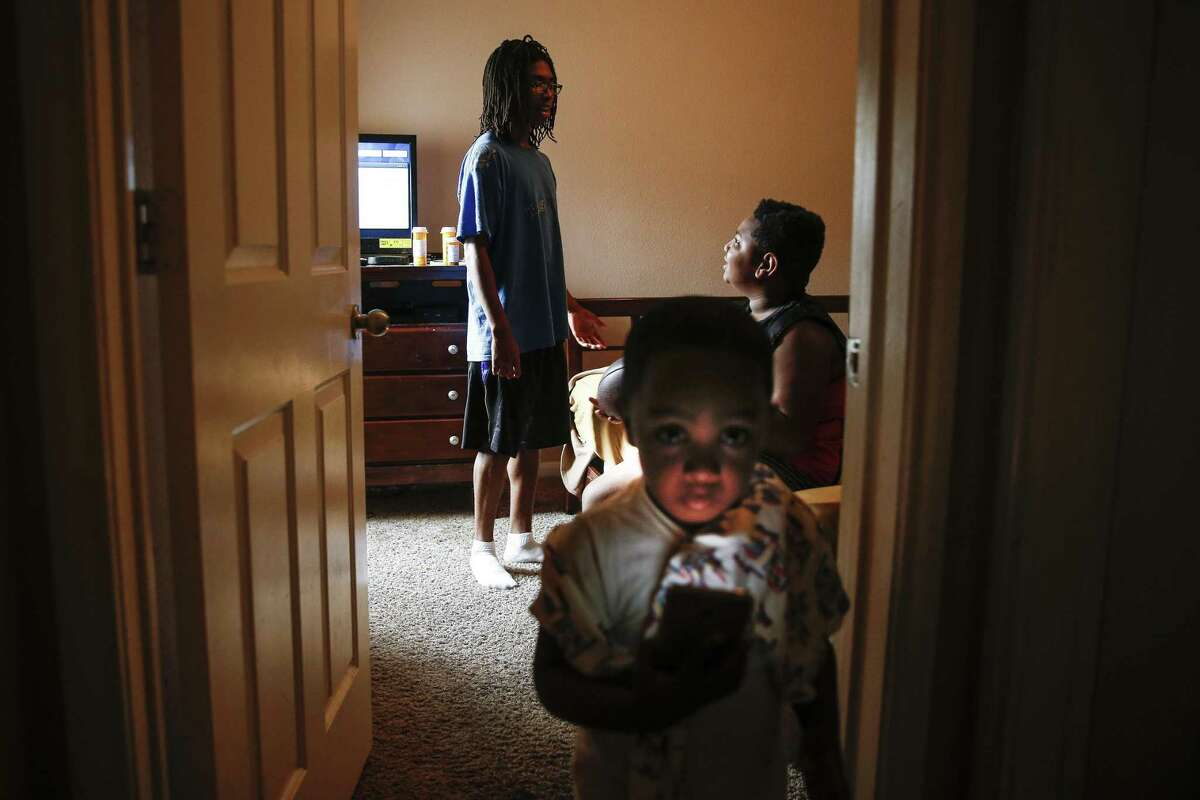 Rashad Jones, 17, left, who relies on Medicaid to cover treatments for his sickle cell anemia, talks to his brothers, Rasheed Jones, 9, right, and Dwight Meggs, 3, left, play in his room Thursday, June 29, 2017 in Houston. Rashad's family worries that if passed, the Senate health care bill could limit access to care. ( Michael Ciaglo / Houston Chronicle )