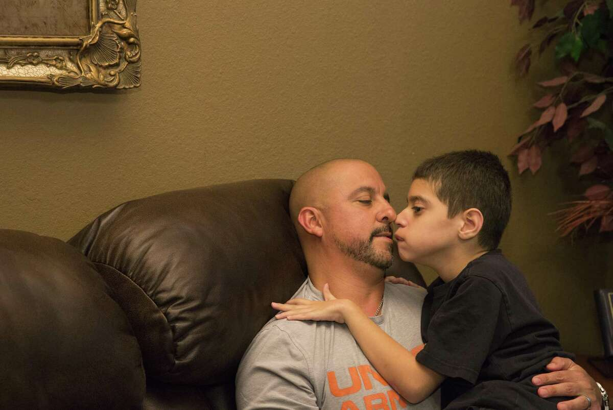 Nicholas Cantu, 9, gives his father, James, a hug after the family played a round of Old Maid card game at home Friday, June 30, 2017, in Spring. Nicholas has significant disabilities after being born premature and his parents are worried that potential reductions to Texas for Medicaid as part of the Senate's bill to repeal and replace the Affordable care Act will chip away at the day to day services they need to not only keep Nicholas alive but also help them manage his care. ( Yi-Chin Lee / Houston Chronicle )