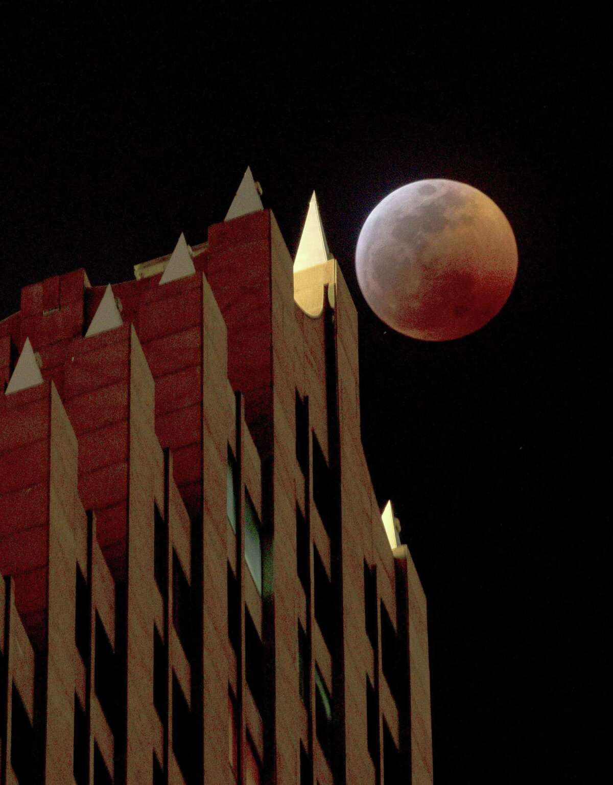 A super blood wolf moon eclipse occurs behind the Bank of America Center building in downtown Houston on Jan. 20, 2019. The moon was fully covered by the Earth's shadow over Houston around 10:30 p.m. that night.