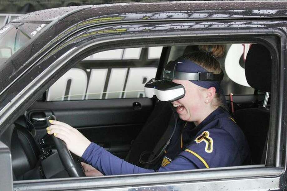 Bad Axe High School Junior Marissa Brown tries out the Arrive Alive driving simulator. The simulator teaches students about the dangers of impaired and distracted driving. (Robert Creenan/Huron Daily Tribune)