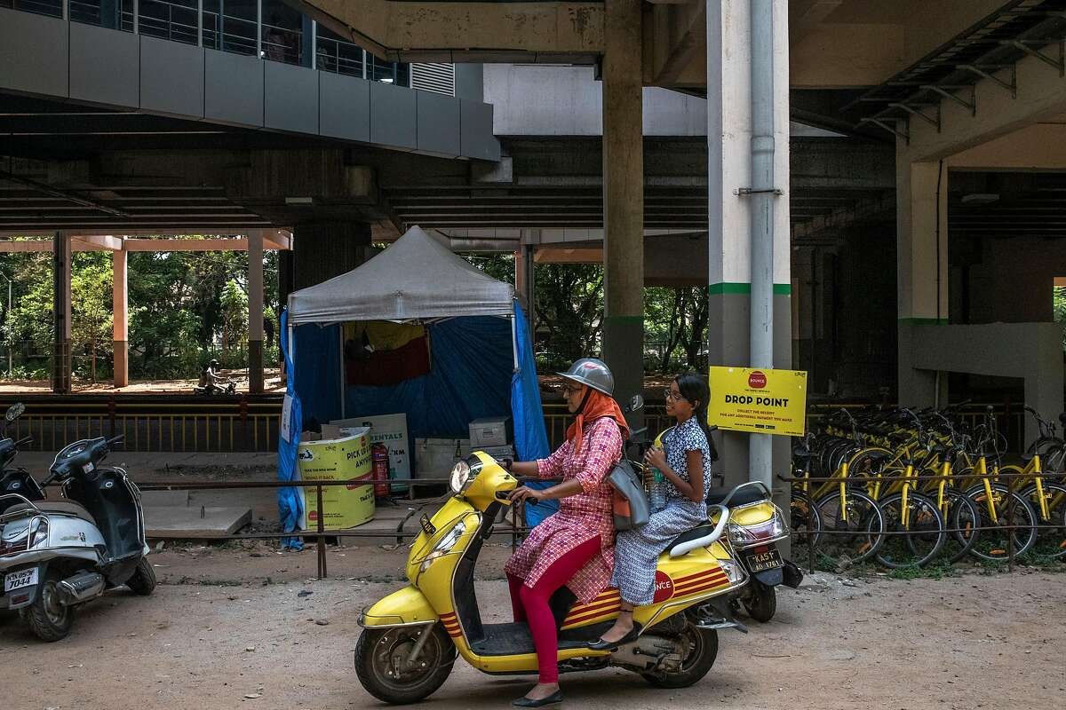Nomita D.P. and her daughter on a rented Bounce scooter after a shopping trip in Bangalore, India, April 25, 2019. Several startups - backed by big Silicon Valley venture firms and Uber's Indian competitor, Ola - are betting that shared motorbikes are better suited to wallets and transportation needs than the cars that are the heart of the ride-hailing industry. (Rebecca Conway/The New York Times)