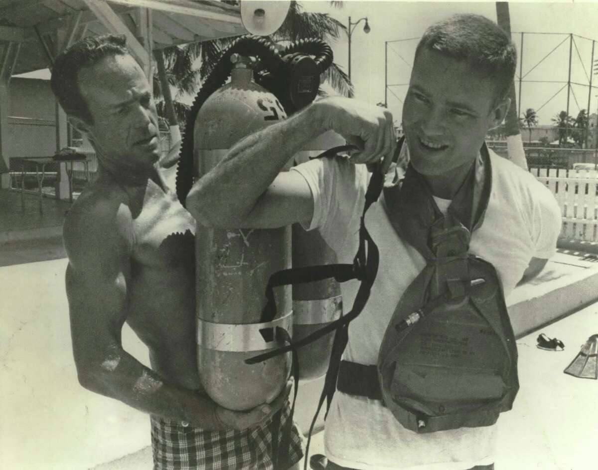 In this 1967 photo, Scott Carpenter, left, the second American to orbit Earth after John Glenn, helps John S. Bull, 32, one of the newest and youngest astronauts at the time, to