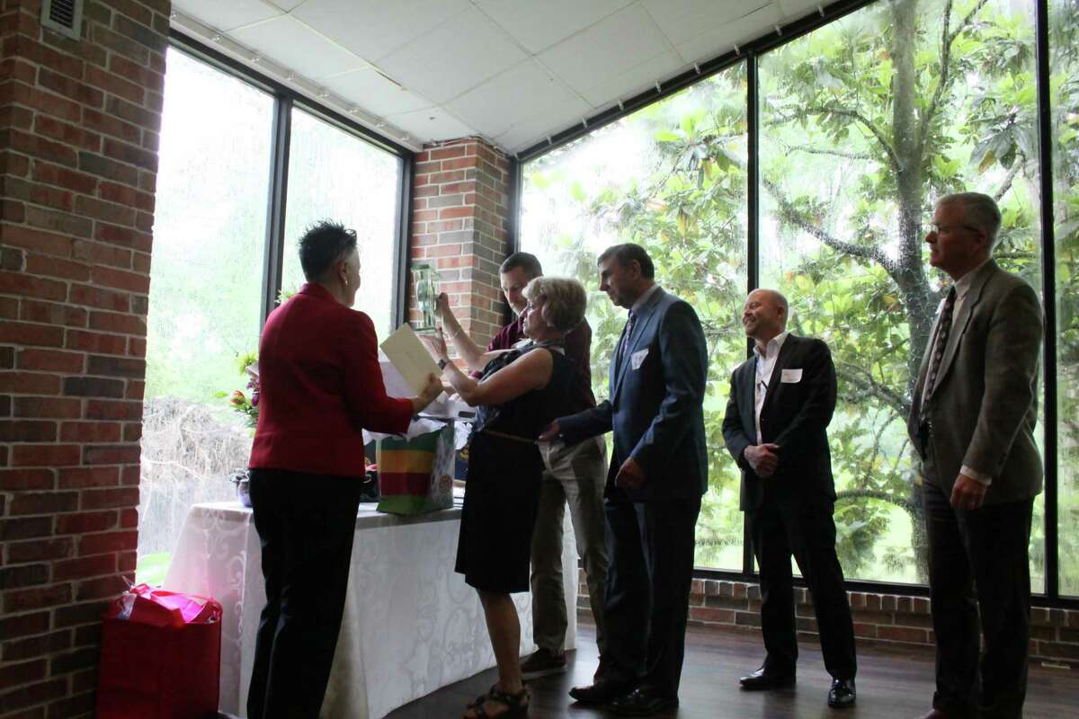 The Houston Northwest Chamber board members present a clock to its retiring president Barbara Thomason during a luncheon on Thursday, May 9, 2019.