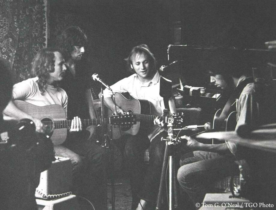"""CSNY - David Crosby (far left), Stephen Stills (center right), Graham Nash (center left) and Neil Young (far right) - rehearse in Studio City in 1969 for Woodstock. """"They renovated Peter Tork's garage by hanging oriental rugs up on the walls for sound,"""" recalled photographer Tom O'Neal. Photo: Tom G. O'Neal / TGO Photo"""