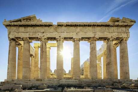 The Parthenon on the Athenian Acropolis, Sun shining through the columns. The Temple is dedicated to the Greek Goddess Athena. Athens, Greece.