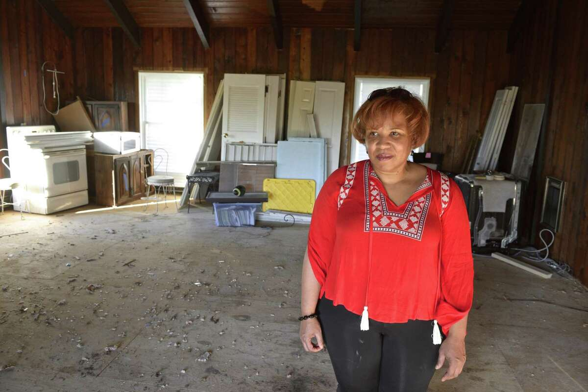Gina Adams stands in her Brookfield home on Wednesday, nearly a year after a macroburst knocked out power and and devastated houses and properties across the Danbury area.