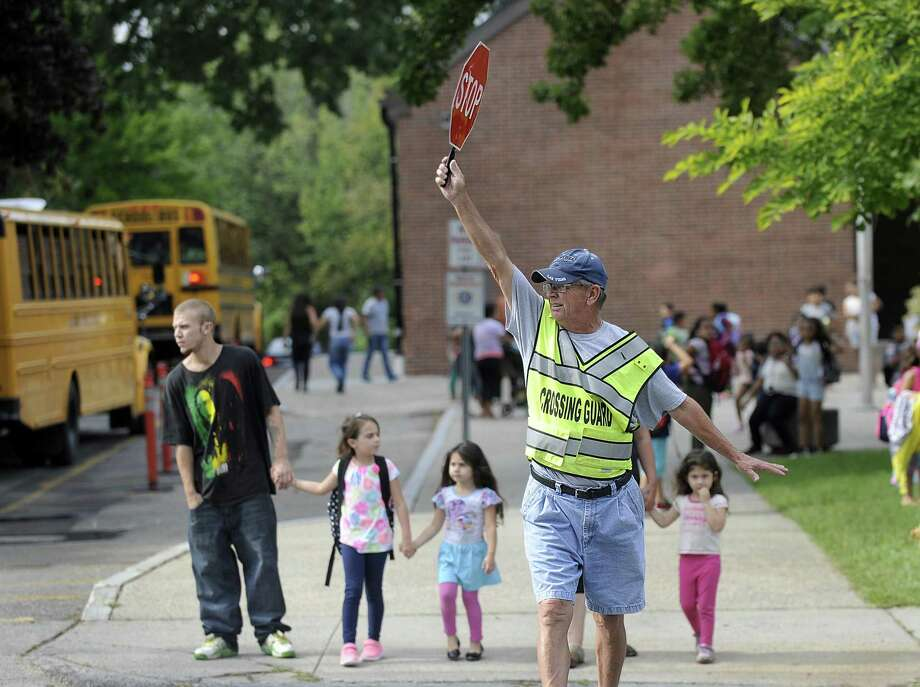 Crossing guard Michael Hawley stops traffic for kids heading home at the end of the school day at South Street School in Danbury on Sept. 1, 2016. Photo: Carol Kaliff / Hearst Connecticut Media / The News-Times