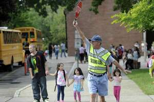 Crossing guard Michael Hawley stops traffic for kids heading home at the end of the school day at South Street School in Danbury on Sept. 1, 2016.