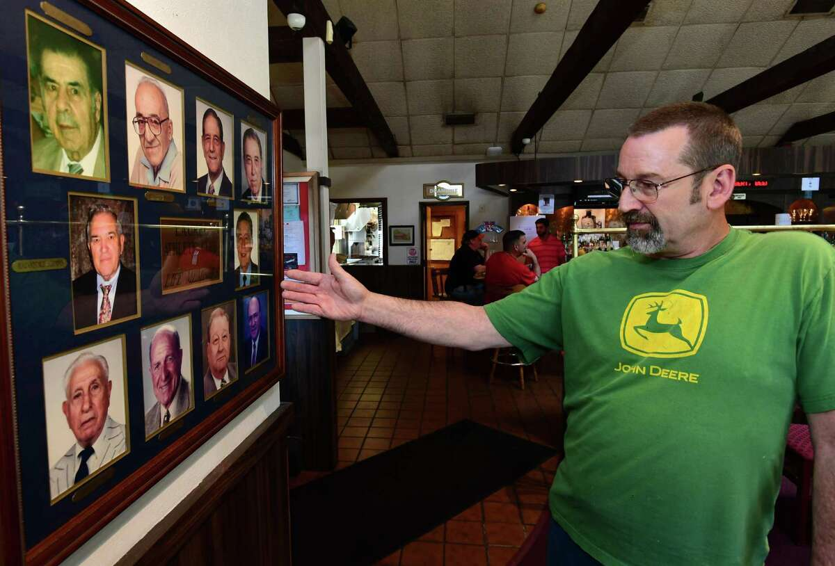 """Laurel Athletic Club president, John """"Skip"""" D'Amato, looks over photos of lifetime members Wednesday, May 8, 2019, at the Club in Norwalk, Conn. The Laurel Athletic Club will celebrate its 100th anniversary on Saturday, May 18, at their 13 North Ave. location where the public is invited to join members of Norwalk's oldest athletic club for a buffet dinner and cocktails as they celebrate a century of memories. Tickets cost $75 per person, which includes dinner, open bar and entertainment courtesy of Tony Massi and The Summertime Band."""