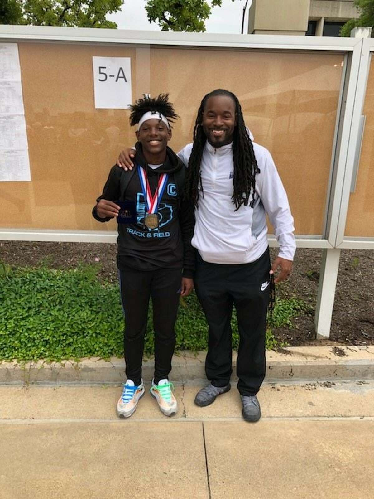 Sterling's Trey Thomas (left) shares a moment with coach Dexter Addison after winning bronze in the Class 5A boys long jump at the UIL state track and field championships at Mike A. Myers Stadium at the University of Texas in Austin.