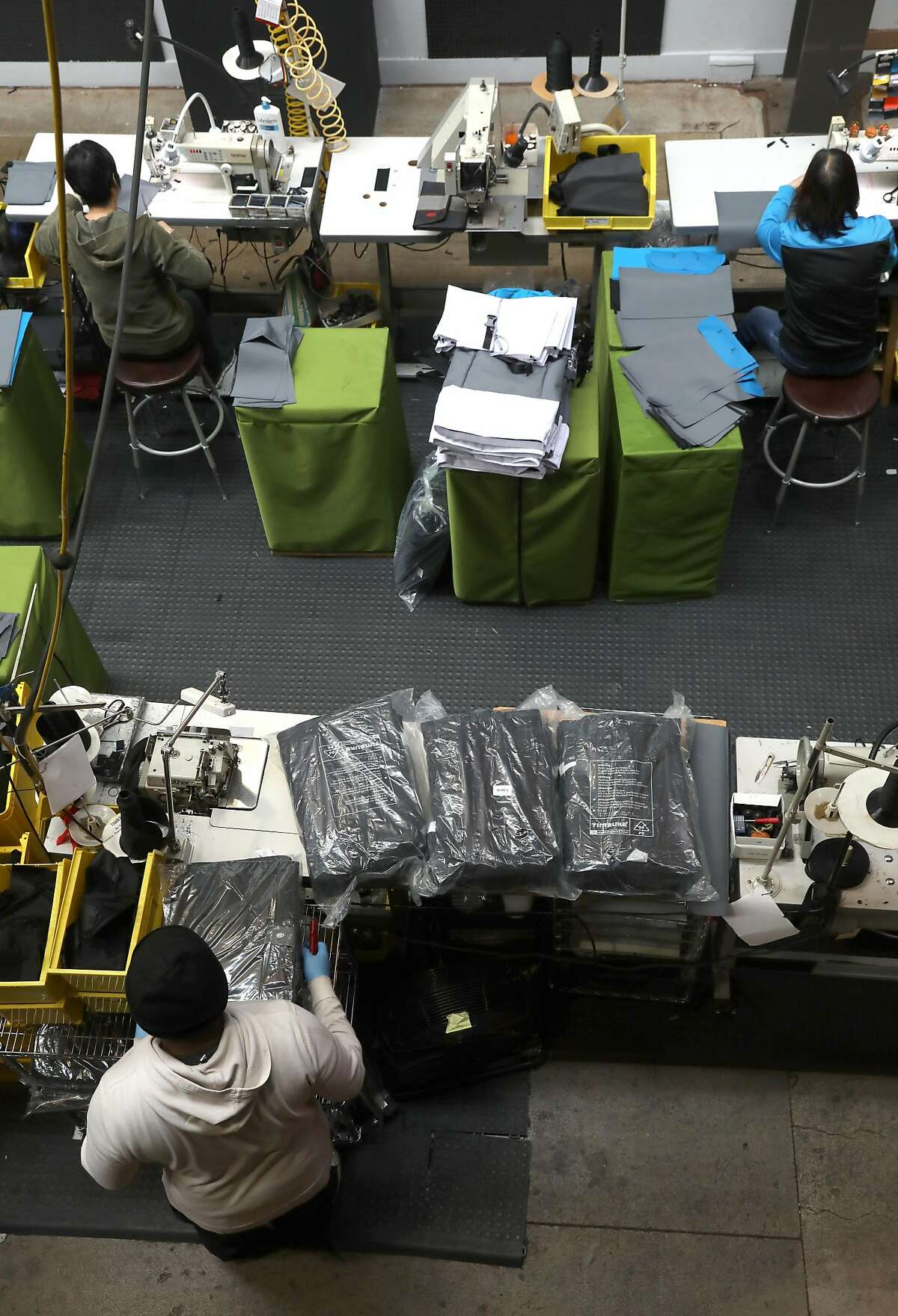 Sewers assemble bags in the factory at Timbuk2 on Thursday, April 11, 2019, in San Francisco, Calif.