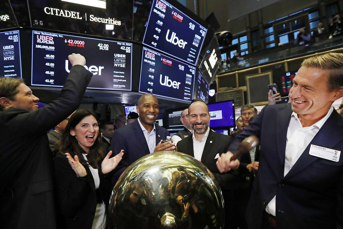Uber board member Ryan Graves, right, rings a ceremonial bell as the company's stock opens for trading during its initial public offering at the New York Stock Exchange, Friday, May 10, 2019. Stacey Cunningham, second from left, president of the NYSE, Tony West, center, Uber's Chief Legal Officer, and CEO Dara Khosrowshahi, second from right, applaud. (AP Photo/Richard Drew)