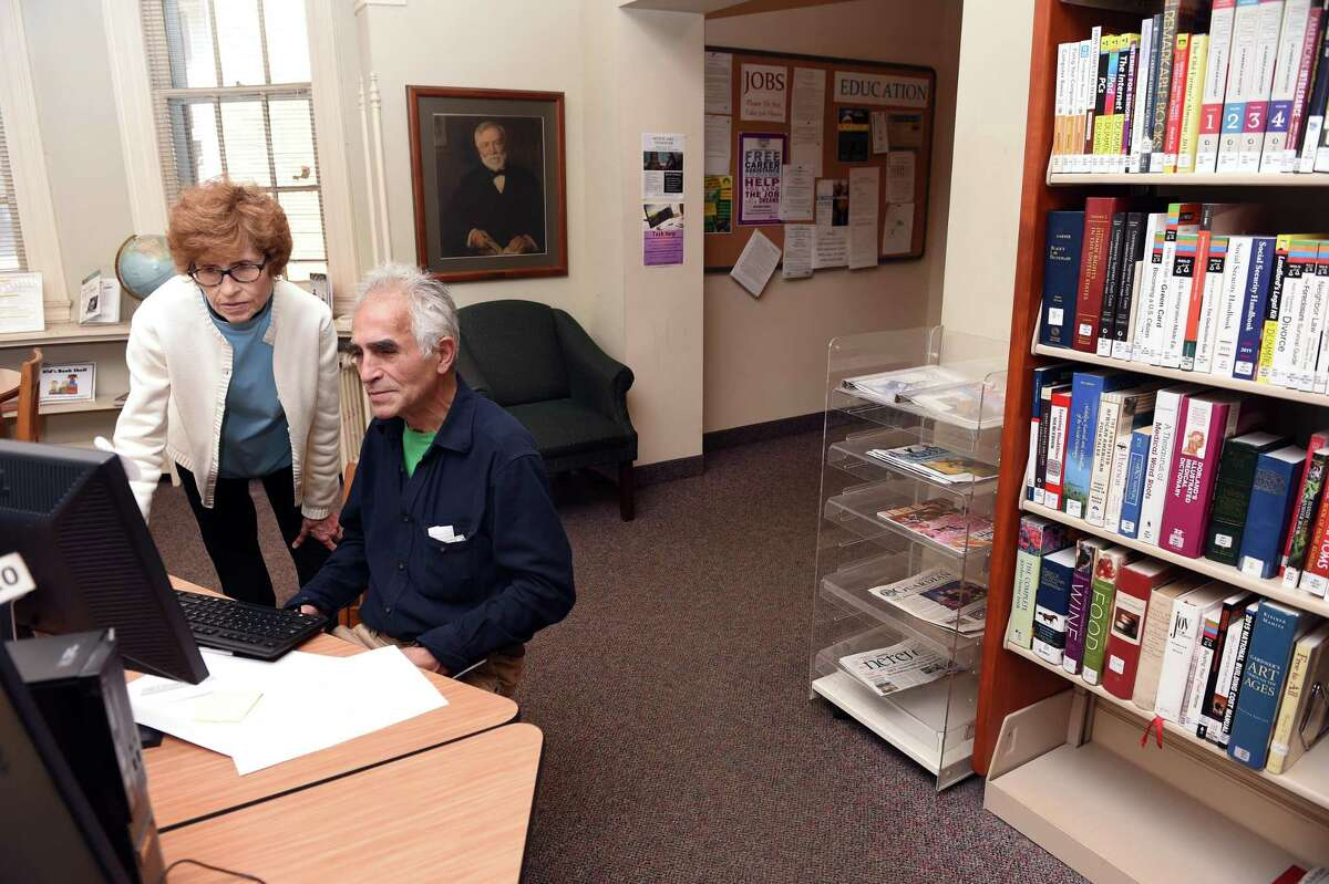 Reference assistant Peggy Dolan, left, helps Luis Alfonso Alvarez of West Haven on a computer in the reference room of the West Haven Main Public .