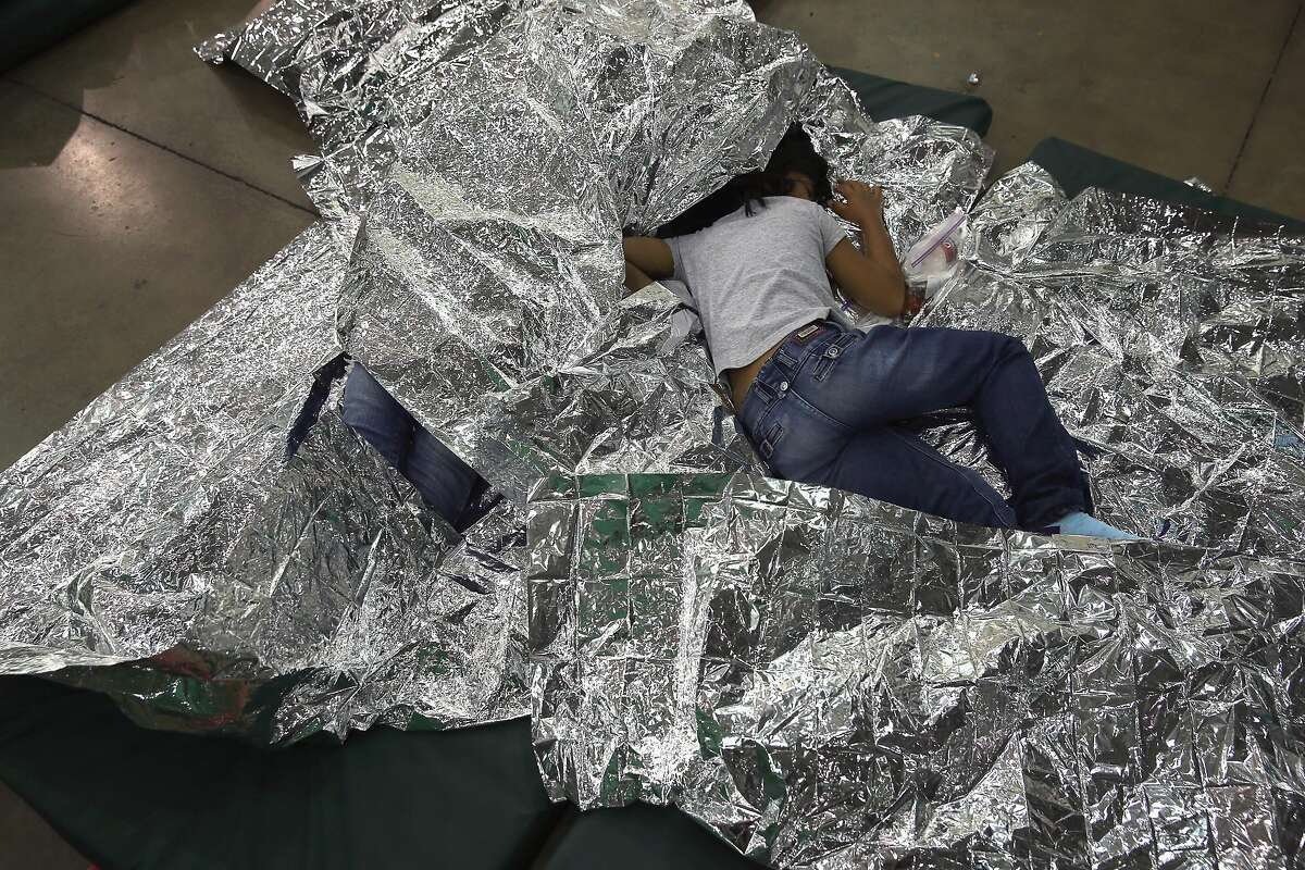 MCALLEN, TX - SEPTEMBER 08: A girl from Central America rests on thermal blankets at a detention facility run by the U.S. Border Patrol on September 8, 2014 in McAllen, Texas. The Border Patrol opened the holding center to temporarily house the children
