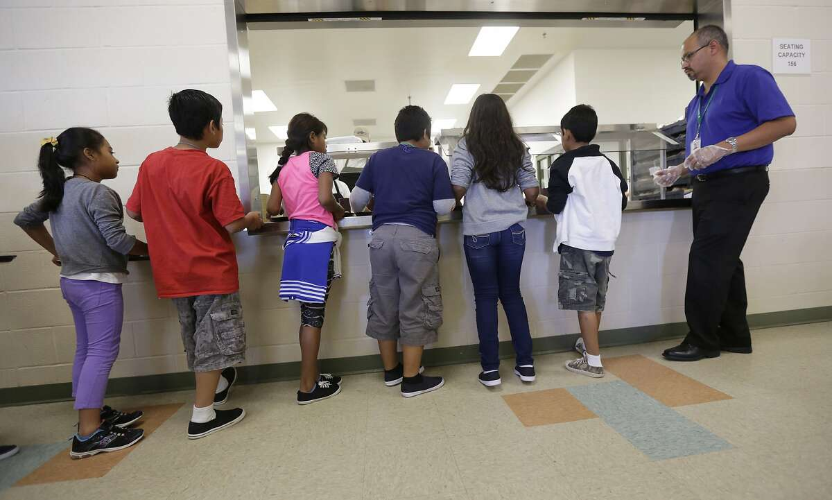 FILE - In this Sept. 10, 2014, file photo, detained immigrant children line up in the cafeteria at the Karnes County Residential Center, a detention center for immigrant families, in Karnes City, Texas. The Trump administration stopped using the center to hold parents and children in March 2019. It's cut back on family detention even as it complains it has to