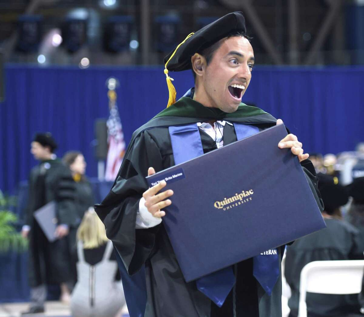 Yuri Brito shows off his Doctor of Medicine degree at the Frank H. Netter MD School of Medicine Commencement Exercises at Quinnipiac University's People's United Center in Hamden on May 10, 2019.