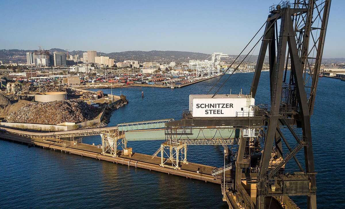 A crane and a conveyor belt rise over the Oakland Estuary at Schnitzer Steel's recycling yard on Monday, Sept. 17, 2018, in Oakland, Calif. Behind the is the Charles P. Howard Terminal which is a proposed location for a new Oakland Athletics ballpark.