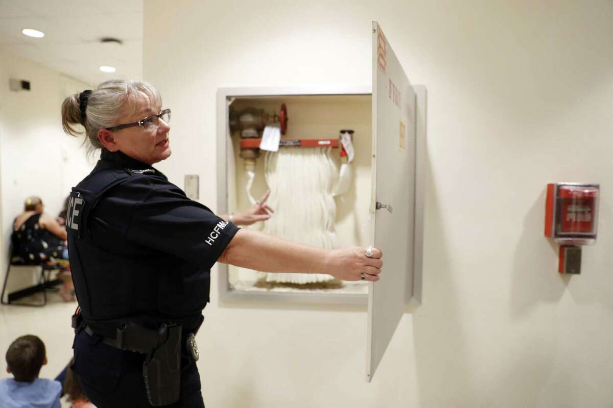 Harris County Fire Inspector Kari Welch checks one of the fire hose boxes while on her rounds at the Family Law Center, in Houston, Tuesday, May 7, 2019. The county had planned to demolish the aging building, but damage to the criminal justice complex during Hurricane Harvey forced courtrooms to be relocated there.
