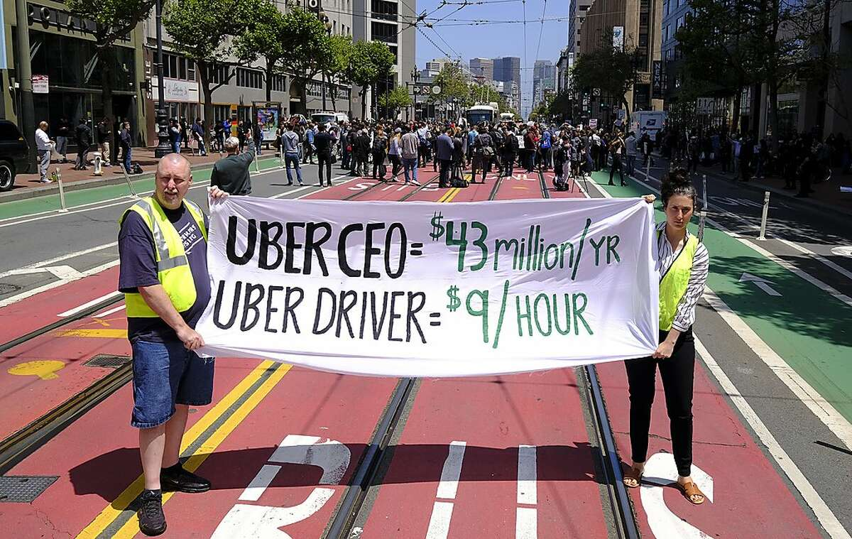 Protesters stop traffic on Market Street during a demonstration outside of Uber headquarters Wednesday, May 8, 2019, in San Francisco. Some drivers for ride-hailing giants Uber and Lyft turned off their apps to protest what they say are declining wages as both companies rake in billions of dollars from investors. Demonstrations in 10 U.S. cities took place Wednesday, including New York, Chicago, Los Angeles, San Francisco and Washington, D.C. The protests take place just before Uber becomes a publicly traded company Friday. (AP Photo/Eric Risberg)