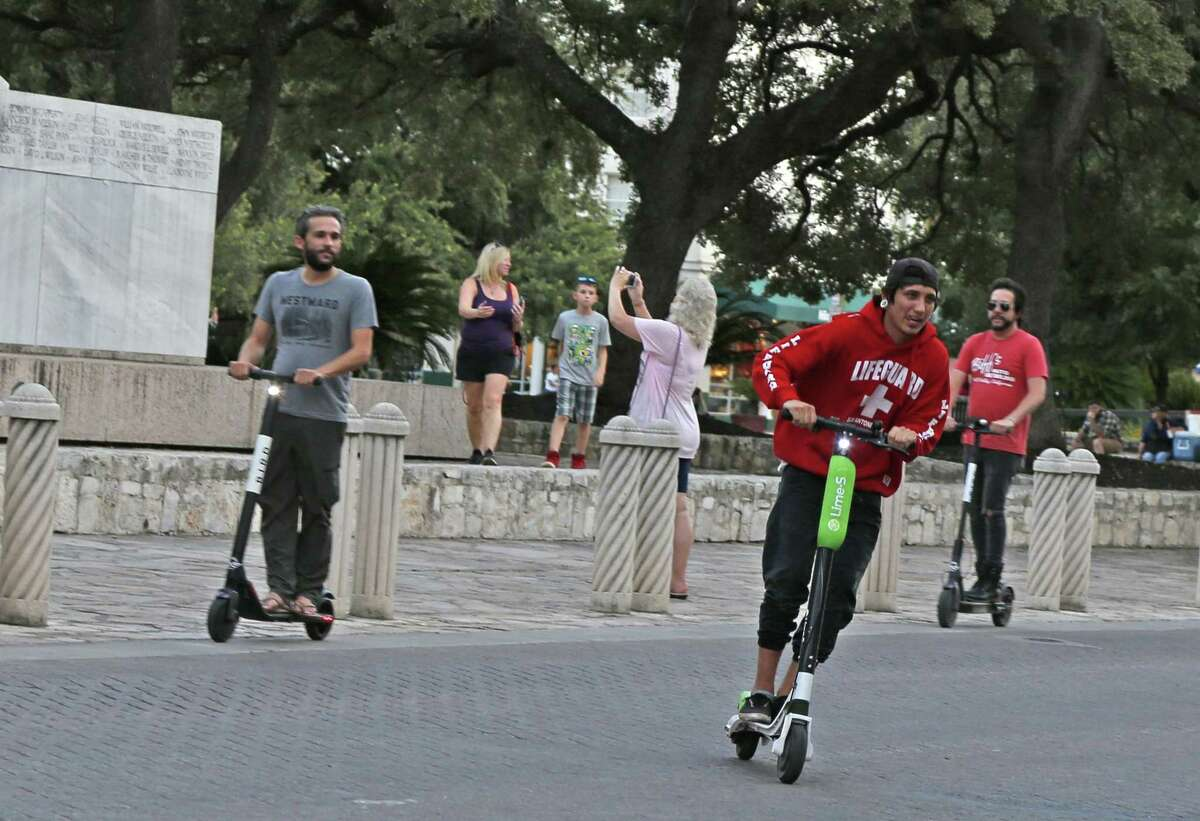 Scooters riders cross Alamo Street in San Antonio. The city is considering measures to better regulate the electric vehicles that have taken over downtown sidewalks.
