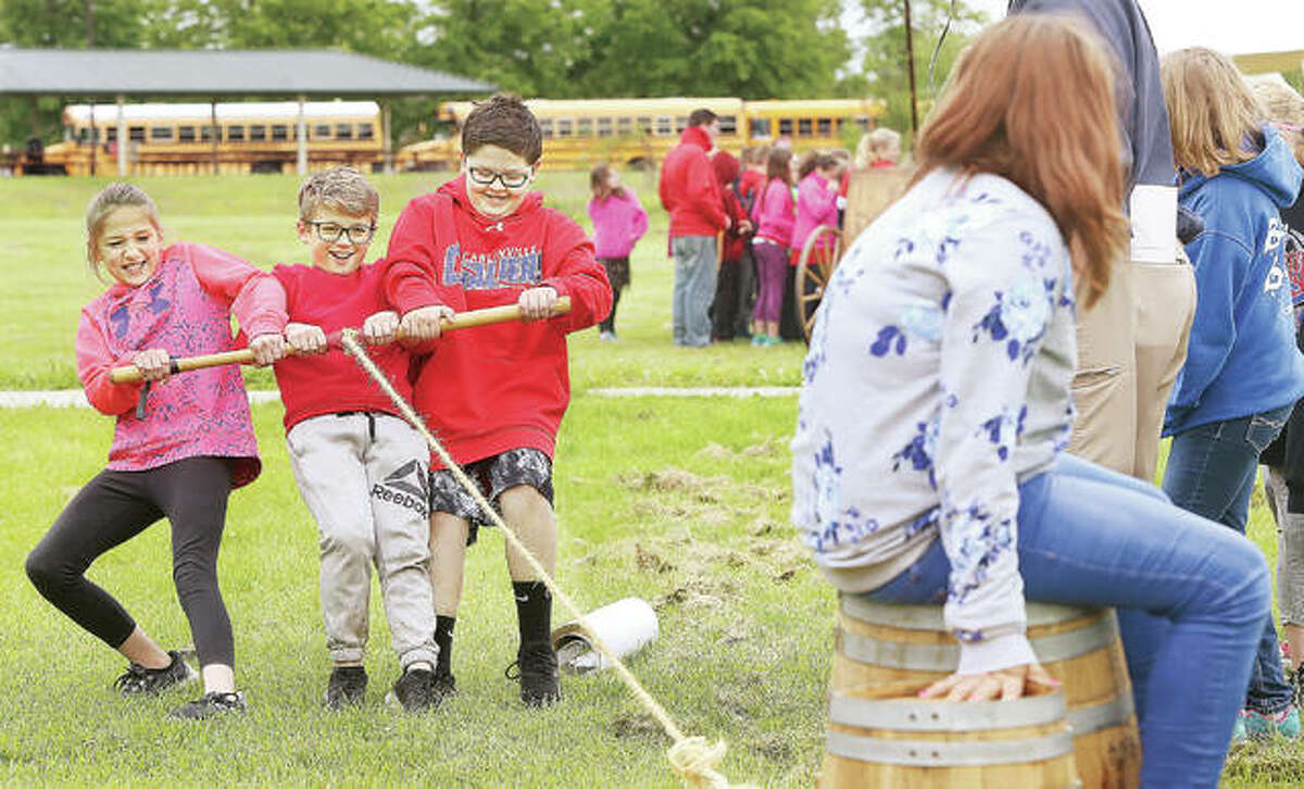 Students from Carlinville Intermediate School try to pull a fellow student sitting on barrels as a demonstration of teamwork Friday at events to commemorate Lewis and Clark's departure day. The student on the barrels was to represent a sick member of the expedition and how they might have had to carry them. The event, which marks the Corps of Discovery departure date of May 14, 1804, was held at Camp Dubois at the Lewis and Clark Historic Site in Hartford. School students from all over the area attended to participate in a number of related events.
