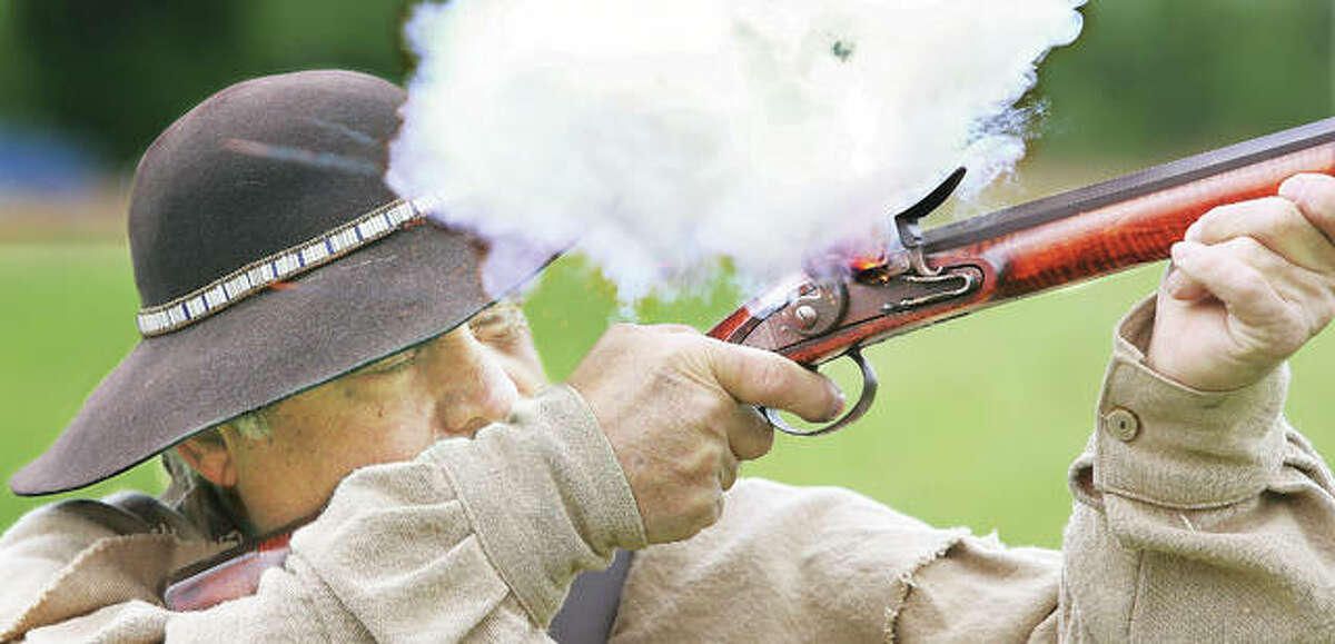 Ed Hamberg of Alton demonstrates a smooth bore, flintlock long gun for students at the event.