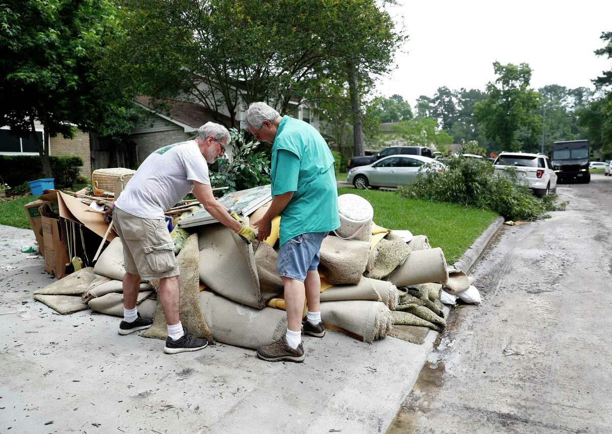 Homeowner David Schoeneck, right, and Doyle Theimer cut a piece of soggy carpet, to save for insurance purposes while they and other residents in the Elm Grove subdivision, in Kingwood, cleaned up, May 9.