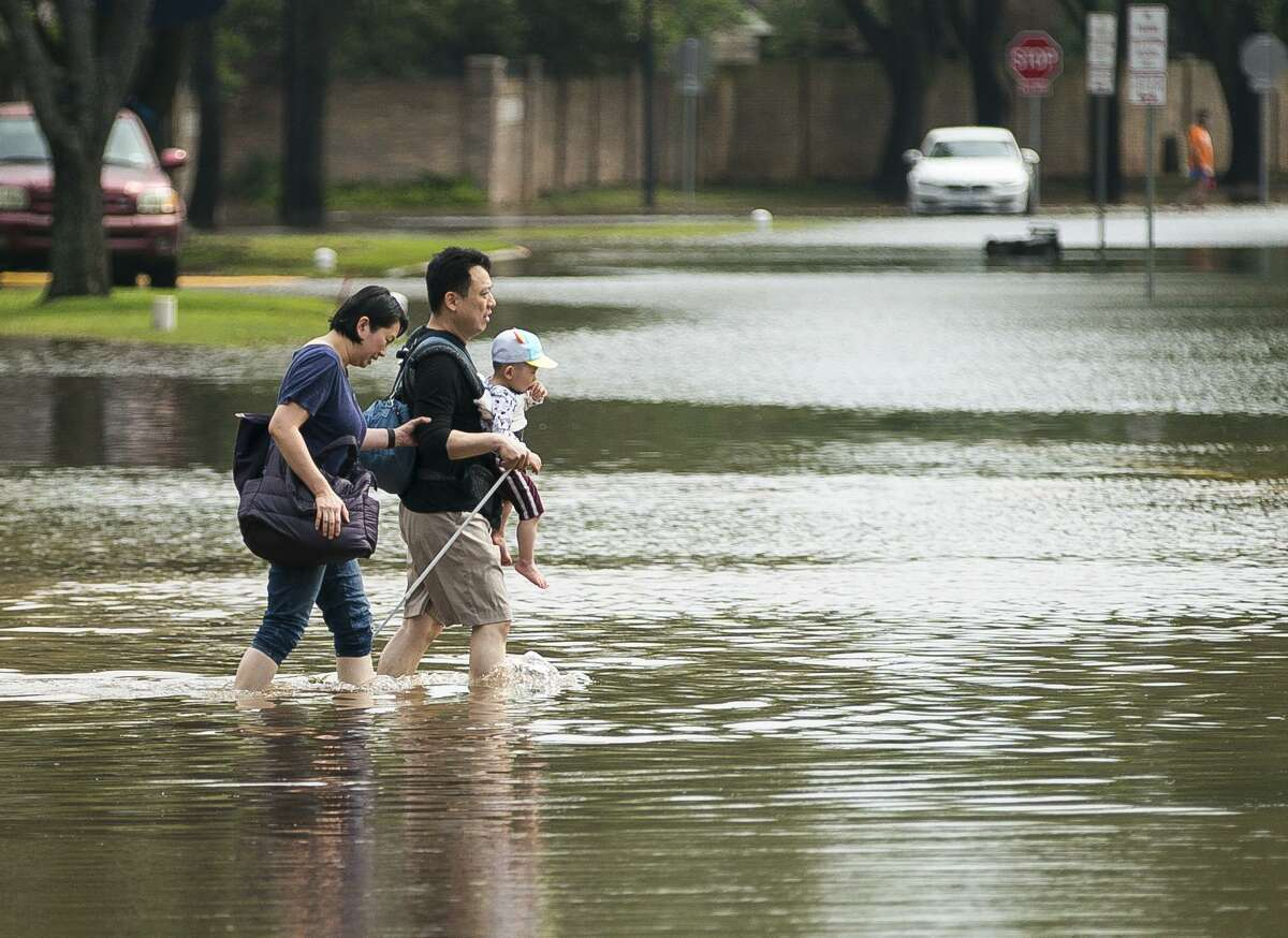 Hsien-Min Yeh, his wife, Julie, and their 20-month-old baby Winston, walk down Austin Parkway at Sweetwater Blvd. back to their home after spending the night in their car in a church parking lot in the Colony Bend area of Sugar Land, Wednesday, May 8, 2019. The family was could not get through to their home during the heavy rain of Tuesday night and pulled into the parking lot of St. Laurence Catholic Church. Residents have been surprised that the water has not receded more quickly as it has in the past when the rain has stopped. In a video released Wednesday morning, the mayor of Sugar Land told residents that levees to the Brazos River had been closed, and that water was now being pumped over the levees into the Brazos, making the water recede much more slowly. More rain is forecast for the coming days.