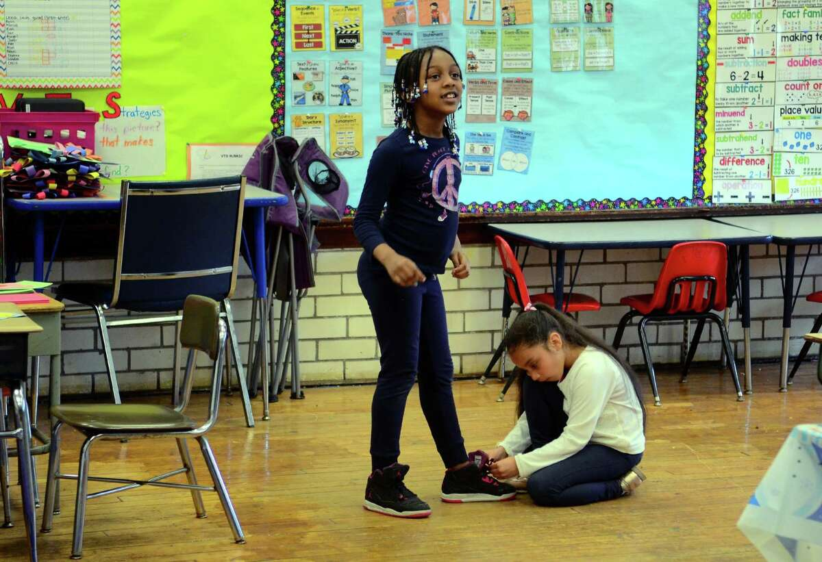 Student Cesia Velez helps tie the shoe of her classmate Keyanna Smith during class at Hall School on Clermont Ave on the East End in Bridgeport, Conn., on Friday May 10, 2019. Due to a city council decision to underfund the district, this school may face closure.