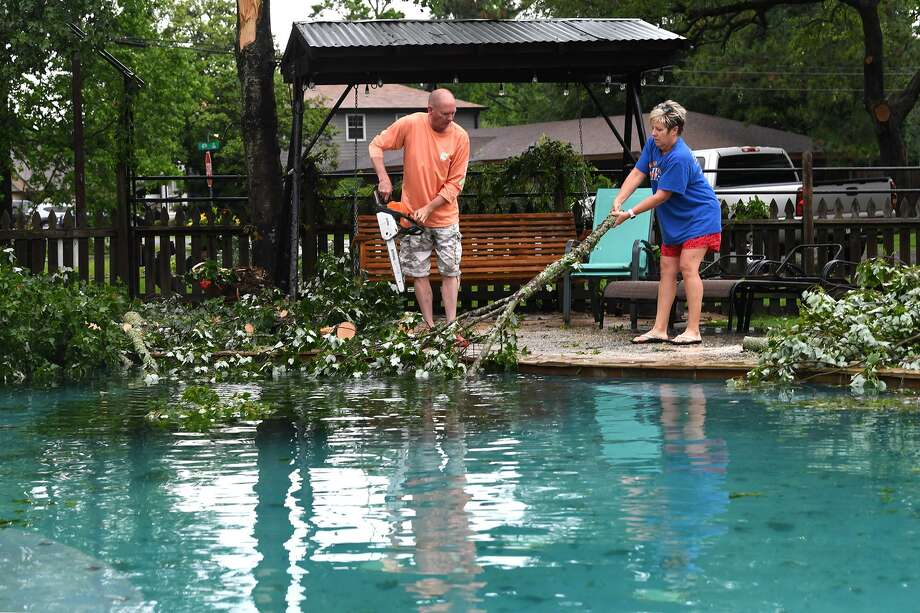 Doyle Coward helps Donna Smith retrieve limbs from the pool of her Port Neches home after Thursday night's storm. Photo taken Friday, 5/10/19 Photo: Guiseppe Barranco/The Enterprise, Photo Editor / Guiseppe Barranco ©