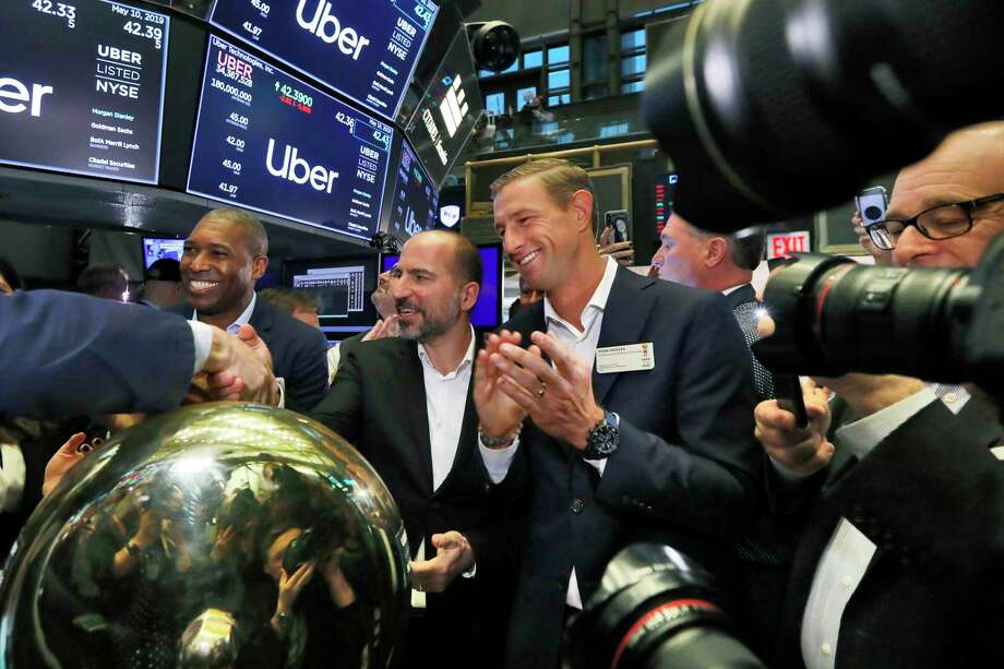 Uber CEO Dara Khosrowshahi center, shakes hands with a trader after his company's initial public offering begins trading at the New York Stock Exchange, Friday, May 10, 2019. He is flanked by Uber's Chief Legal Officer Tony West, left, and board member Ryan Graves, right. (AP Photo/Richard Drew) Photo: Richard Drew / Copyright 2019 The Associated Press. All rights reserved