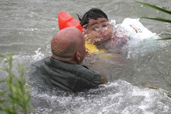 A Border Patrol Agent rescues a seven year old boy from Honduras after he fell out of a make shift raft and lost hold of his mother as Border Patrol agents respond to three rafts crossing the Rio Grande River in Eagle Pass, on Friday, May 10, 2019.