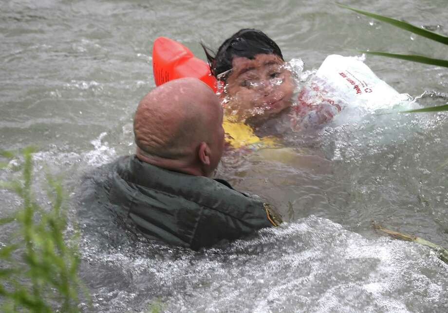 A Border Patrol Agent rescues a seven year old boy from Honduras after he fell out of a make shift raft and lost hold of his mother as Border Patrol agents respond to three rafts crossing the Rio Grande River in Eagle Pass, on Friday, May 10, 2019. Photo: Bob Owen / ©2019 San Antonio Express-News