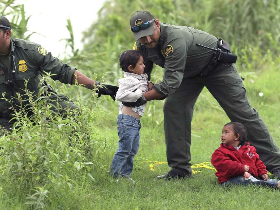 Border Patrol agents lift the young children onto the grassy shore, which is lined by tall carrizo cane. Photo: Bob Owen / ©2019 San Antonio Express-News