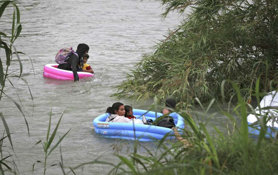 The group of nine migrants from Honduras and El Salvador almost made it across the swollen river the inflatable pools before two tipped over. Agents on the riverbank tossed rescue ropes to help them get on dry land. Two agents jumped in to help them. Photo: Bob Owen / ©2019 San Antonio Express-News