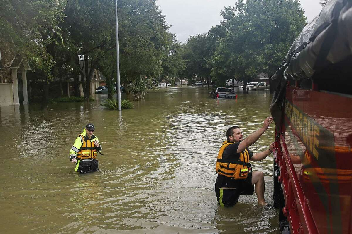 Cy-Fair volunteer firefighters climb back into their truck after following up on a call as Addicks Reservoir surpasses capacity due to near constant rain from Tropical Storm Harvey Tuesday, Aug. 29, 2017 in Houston.