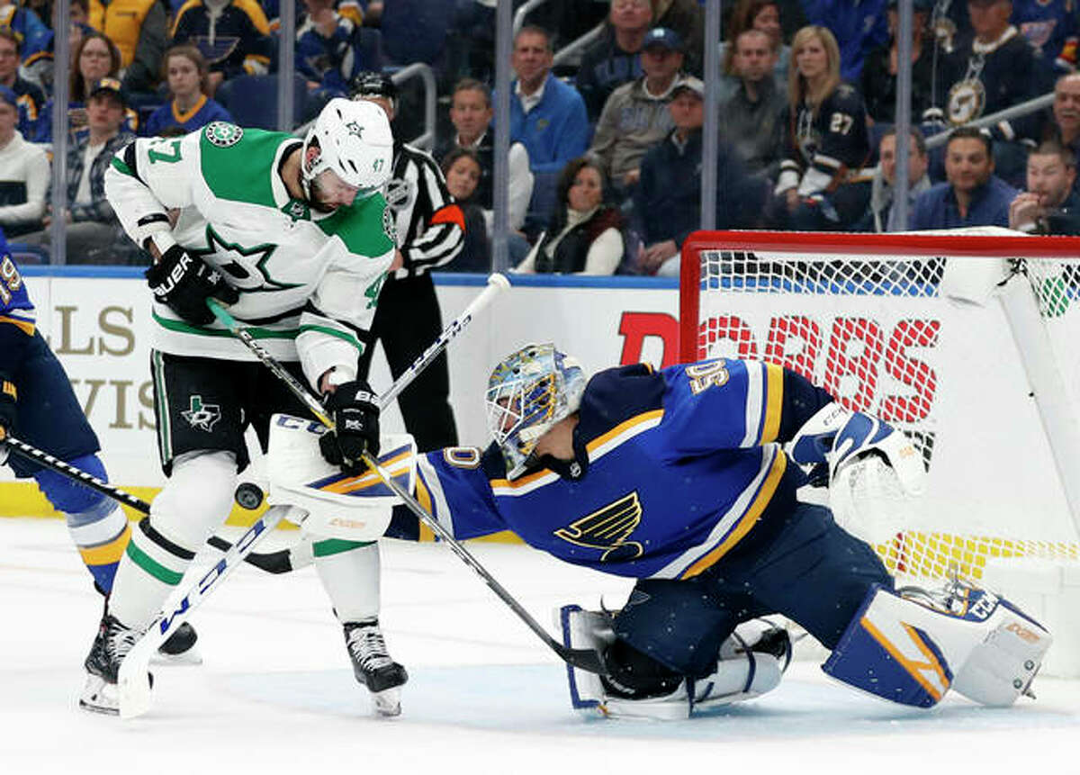 Blues goalie Jordan Binnington (50) attempts to clear an airborne puck as Alexander Radulov of Dallas (47) pressures the net during a Stanley Cup playoffs Western Conference semifinal game.