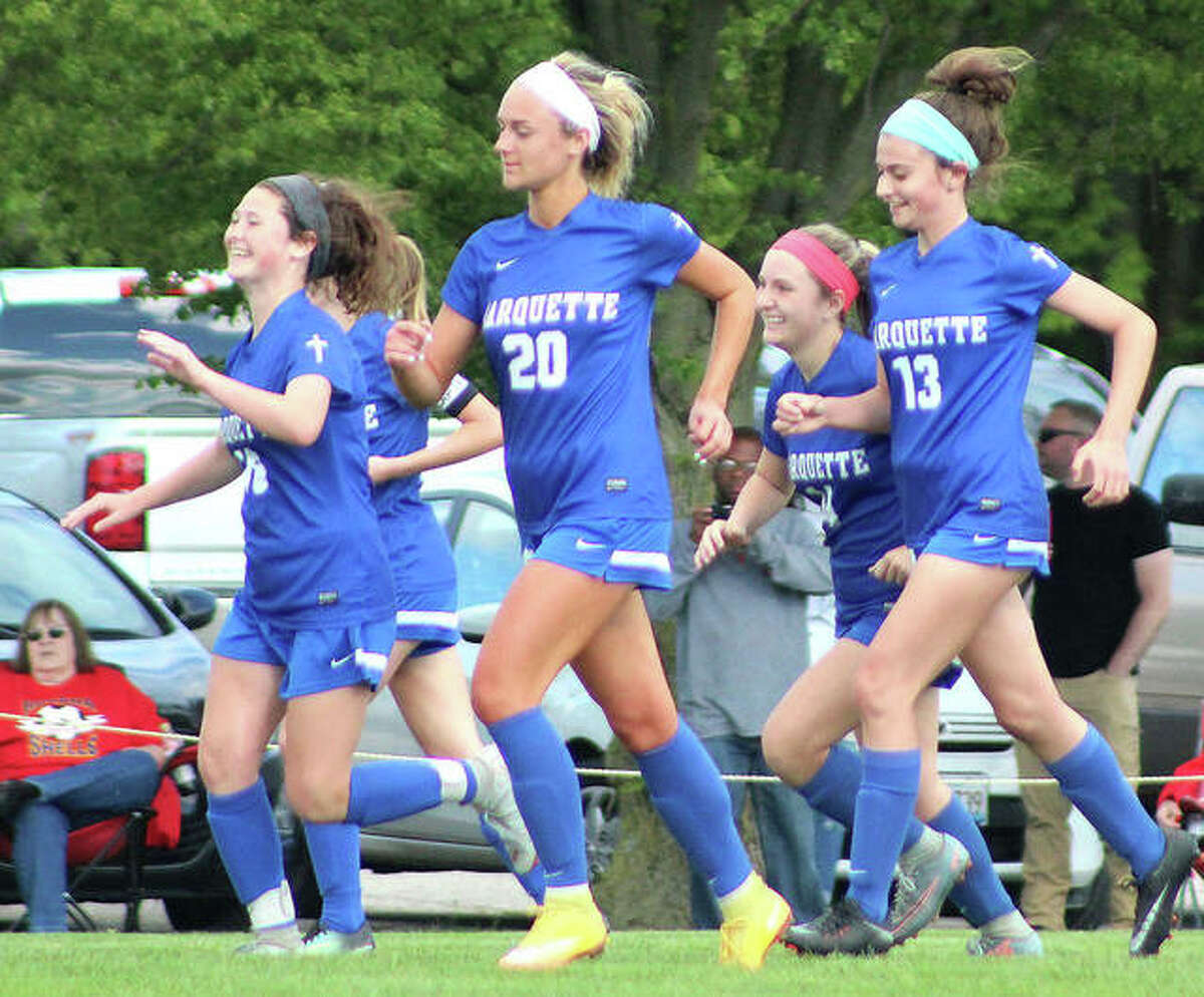 A group of Marquette players are all smiles as they head back upfield following a goal during their regional title game victory over Roxana Friday at Gordon Moore Park. From left are Madelyn Smith, Chloe Kane, Anna Rodgers and Elli Jacobs.