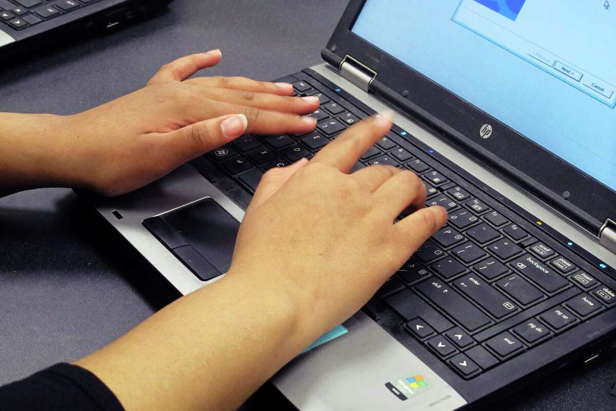 In this March 13, 2019, photo. a Bennett High School student re-images a laptop in a school computer lab in Buffalo, N.Y.