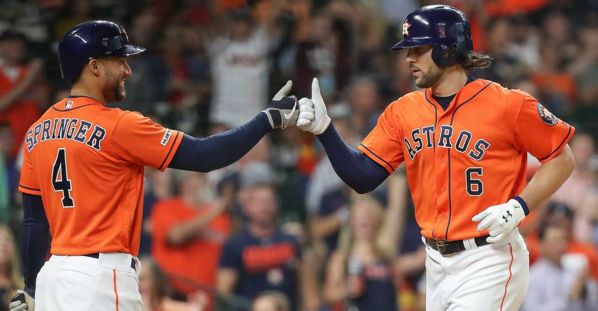 Houston Astros center fielder George Springer (4) fist bumps Houston Astros center fielder Jake Marisnick (6) after he hit a homer run during against the Texas Rangers at Minute Maid Park Friday, May 10, 2019, in Houston.
