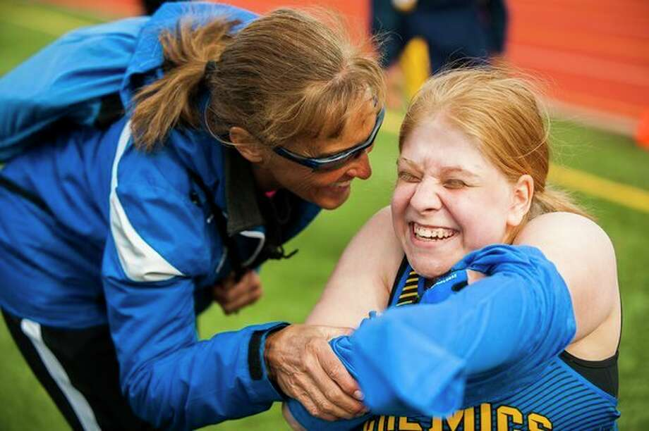FILE — Midland High head girls' track coach Diane Sugnet congratulates sophomore FaithAnne Sawicki after she competed in the 100-meter dash in her wheelchair during a track meet on Tuesday at Midland Community Stadium. (Katy Kildee/kkildee@mdn.net)