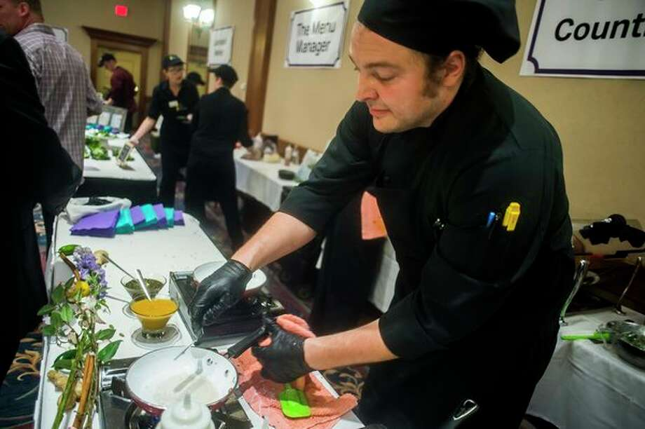 Midland Country Club Executive Chef Nate Sell prepares an Indian-inspired dish during the Chefs for Shelterhouse annual fundraiser Thursday at the Great Hall Banquet & Convention Center. (Katy Kildee/kkildee@mdn.net)