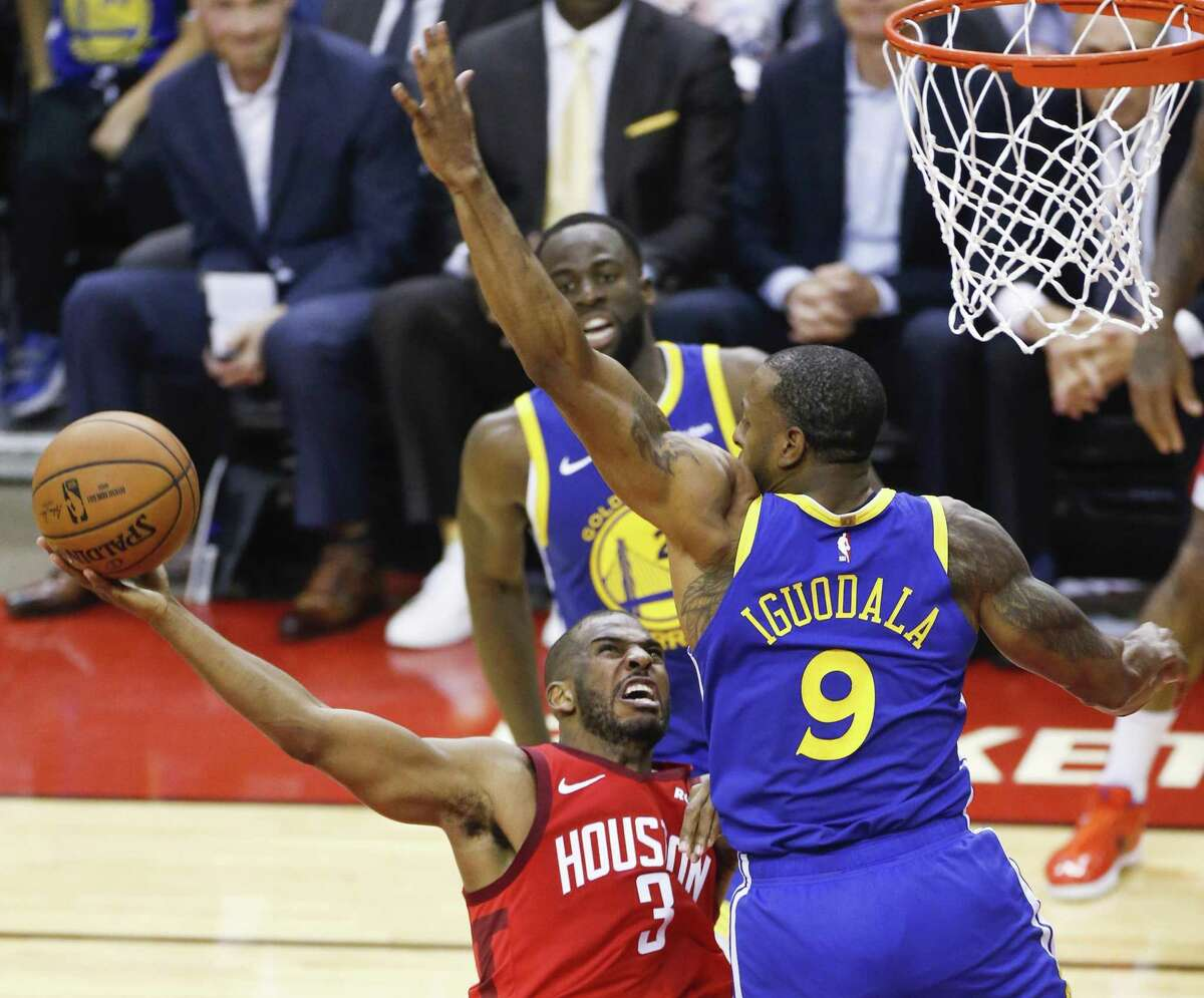 Rockets guard Chris Paul, left, takes a shot against the defense of Warriors guard Andre Iguodala during the second half. Paul had 27 points along with 11 rebounds and six assists.