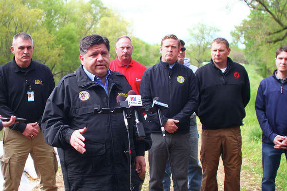 Gov. J.B. Pritzker speaks during a press conference on one of the levees along the Illinois River in Meredosia. Photo: Rosalind Essig | Journal-Courier