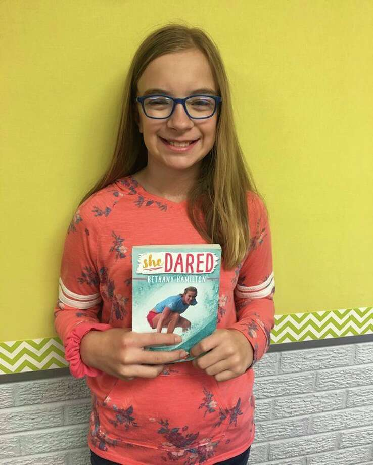 Dana Koth is pictured with her favorite book, 'She Dared,' which is the inspirational true story of Bethany Hamilton who lost her arm to a shark attack and yet continues to surf. Koth especially loved this book because her aunt is also named Bethany. (Submitted Photo)
