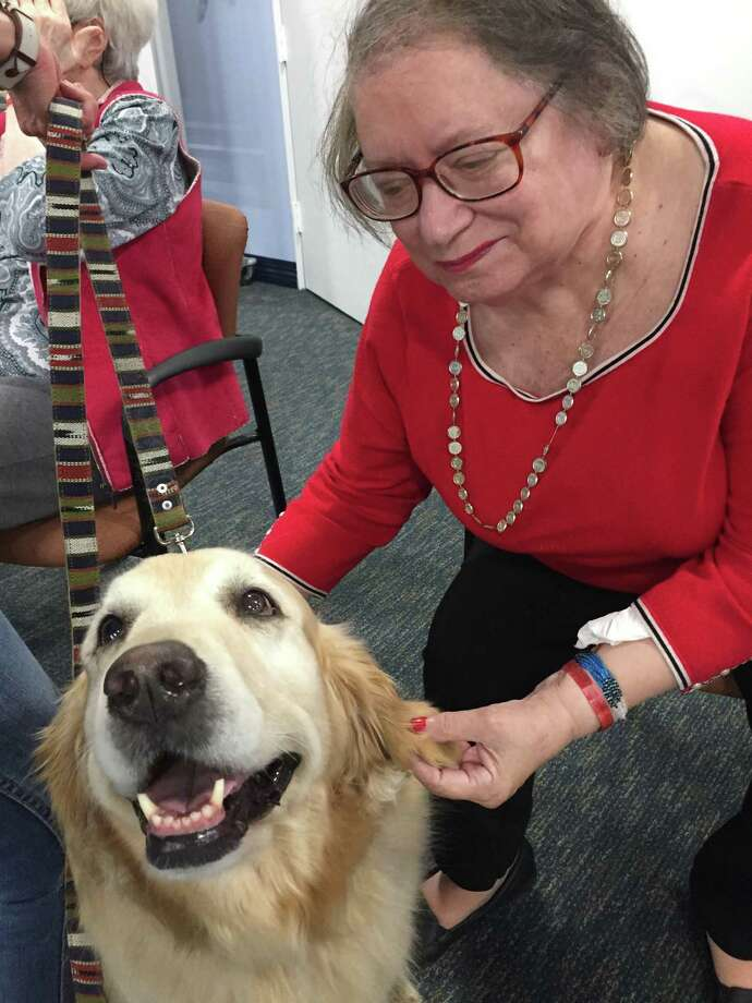 Witherell resident Diane Marinaro with 8-year-old golden retriever Lucy at the Pooch Parade at The Nathaniel Witherell. The event was a big hit last week as eight dogs were paraded around to interact with residents and provide valuable pet therapy, which has been shown to stimulate positive memories and provide a lot of joy. Photo: Contributed