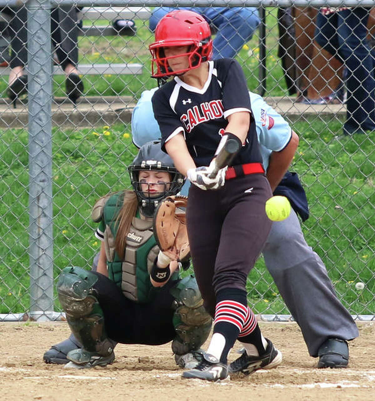 Calhoun's Mackenzie Cranmer makes contact while Carrollton catcher Kennedy Ruyle awaits the pitch during an April 25 game in Carrollton. Cranmer had two RBIs Friday in the Warriors' win at Jacksonville Routt.